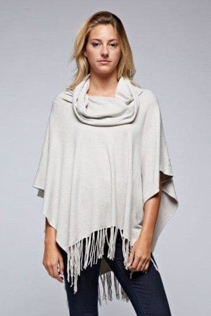 The perfect poncho with fringed hem for year round wear. Made of a buttery soft combination of nylon, viscose and modal this easy cowl neck style is hand washable, lay flat to dry. Also available in grey and black at Liza Byrd in Stevenson Village.